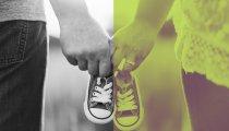 Aikuinen mies ja nainen käsikkäin, kannattelevat pieniä lapsen kenkiä.